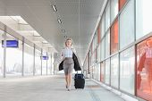 foto of carry-on luggage  - Full length of young businesswoman with luggage rushing in railroad station - JPG