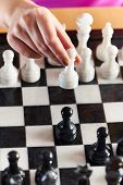picture of chessboard  - Hand with white pawn over chessboard closeup - JPG