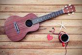 foto of ukulele  - Cup of coffee with ukulele on old wooden background Vintage style - JPG
