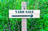 picture of yard sale  - YARD SALE written on Directional wooden sign with arrow pointing to the right against green leaves background - JPG