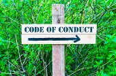 pic of conduction  - CODE OF CONDUCT written on Directional wooden sign with arrow pointing to the right against green leaves background - JPG