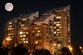 Block Of Flats By Night With Full Moon Above