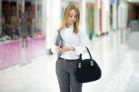 stock photo of running-late  - Beautiful business girl wearing office style outfit holding document dossier and suede bag looking at wristwatch checking time running late or waiting - JPG