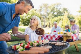 picture of grandparent child  - Happy father doing barbecue with her daughter on a sunny day - JPG