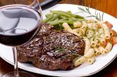 picture of ribeye steak  - a grilled rib eye steak with vegetables pasta and red wine - JPG