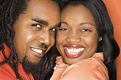 Smiling African-American mid-adult couple wearing orange clothing on orange background.