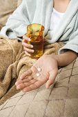 Caucasian/Hispanic young woman holding pills in hand with glass of water.
