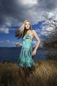 Kaukasische jonge volwassen blonde vrouw in veld op kust met haar swingende uit.