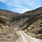 Dirt road winding through rocky desert cliffs of Cottonwood Canyon, Utah.