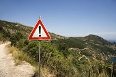 Caution sign on coastal dirt road.