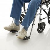 Legs and feet of elderly man sitting in wheelchair.