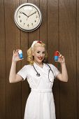 Caucasian mid-adult female nurse standing by wood paneling holding oversized pills and smiling at vi