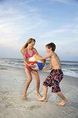 Caucasiano pré-adolescente menino e menina puxando beachball.