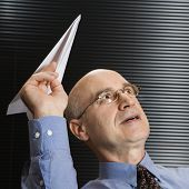 Caucasian middle-aged businessman playing with paper airplane.