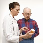 Mid-adult Caucasian female doctor pointing at prescription bottle as elderly Caucasian male looks at bottle.