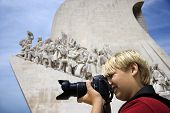 Caucasian boy looking through camera at the Monument to the Discoveries in Lisbon, Portugal.