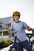 Caucasian pre-teen boy on bicycle wearing helmet looking at viewer.