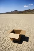 Empty open box in cracked desert landscape in California.
