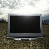 Flat panel television set in grassy field.