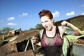 Angry tattooed Caucasian woman yelling with fists clenched in junkyard.
