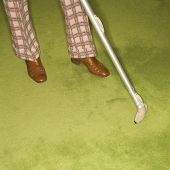 Close-up of Caucasian male feet with vacuum extension against green retro carpet.