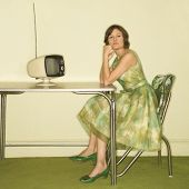 Pretty Caucasian mid-adult woman wearing green vintage dress sitting at 50's retro dinette in front