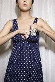 Pretty Caucasian young woman stuffing bra to enhance breast size with tissue.