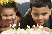Hispanic girl and boy leaning in close looking at lit candles on birthday cake and smiling.
