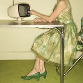 Side view of Caucasian mid-adult woman wearing green vintage dress sitting at 50's retro dinette set
