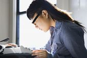 Pretty young Asian woman sitting in chair typing on typewriter in kitchen.