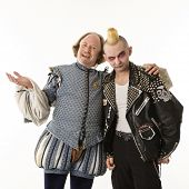 William Shakespeare smiling with arm around gothic punk young man.