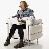William Shakespeare in period clothing sitting on modern chair using laptop.