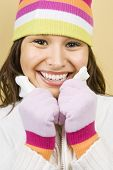Young adult Caucasian woman wearing winter hat and gloves and smiling at viewer.