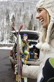 Couple standing with ski equipment by open vehicle smiling and laughing.