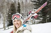 Attractive young blond woman in winter ski gear carrying skis over shoulder smiling.