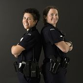 Portrait of two mid adult Caucasian policewomen standing back to back looking over their shoulders s
