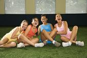 Four multiethnic girls sitting with arms around eachother laughing.
