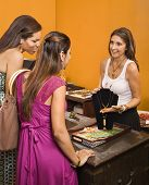 Sales clerk showing necklace to women shoppers in boutique.
