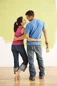 Attractive couple standing in front of partially painted wall with arms around each other smiling.