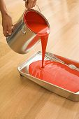 Caucasian woman pouring red paint from can into tray.