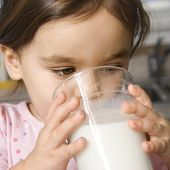 Caucasian girl drinking glass of milk.