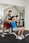 Man assisting woman at gym with hand weights smiling.