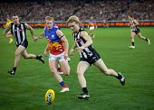 MELBOURNE - AUGUST 20 : Ben Sinclair (front) attacks the ball during Collingwood's  win over Brisban
