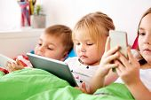 childhood, technology and family concept - little kids with tablet pc computer and smartphones in be poster