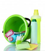 detergent bottles, brushes and sponges in bucket isolated on white