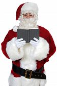 stock photo of reading book  - Santa Claus reading a book over white background - JPG