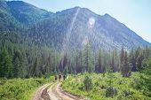 Group Of Travelers With Backpacks Walk Along A Trail Towards A Mountain Ridge By Sunny Day. Backpack poster