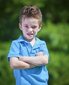 foto of spoiled brat  - Angry boy with crossed arms outdoor portrait - JPG