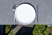 Empty Ceramic Round Plate And Cutlery On Grey Tablecloth Outdoors, Copy Space. Dinner Plate Setting. poster