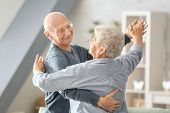 Cute elderly couple dancing at home poster